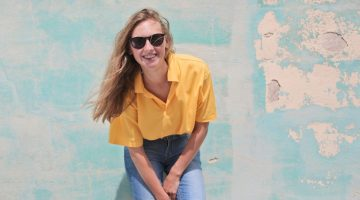 Canva - Woman Wearing Yellow Polo Shirt Standing in Front of Teal Concrete Wall